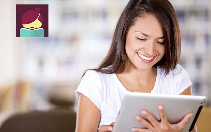woman reading an e-book reader featuring Libby app from Overdrive