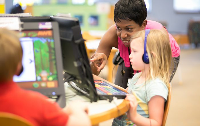 photo of little girl and librarian at computer